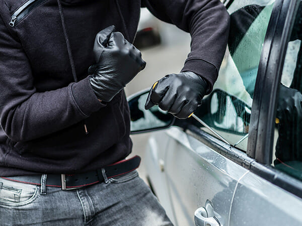 a man in a black jacket and jeans, wearing black gloves trying to break into a gray sedan with a screwdriver as part of our custom car alarm installation.