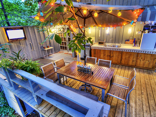 outdoor patio with table and chairs to show custom speaker set up