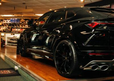 a shot of a black car inside of a showroom
